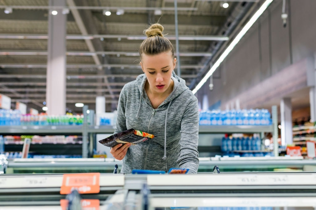 Pregnant Woman buying frozen food and holding a deep-frozen product in a supermarket